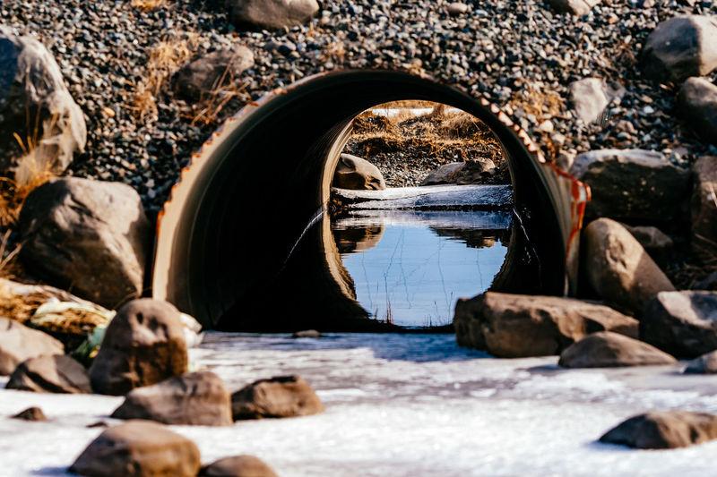 Frozen stream against pipe amidst rocks