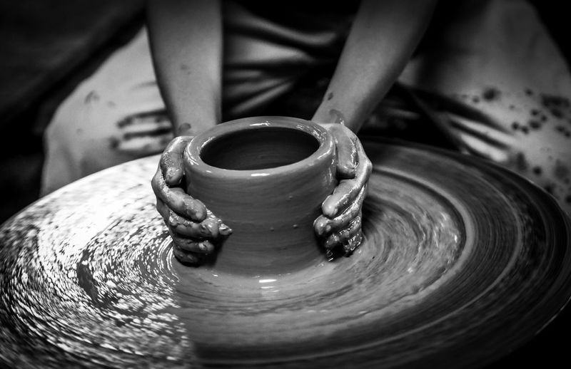 Midsection Of Potter Making Pot On Pottery Wheel At Workshop