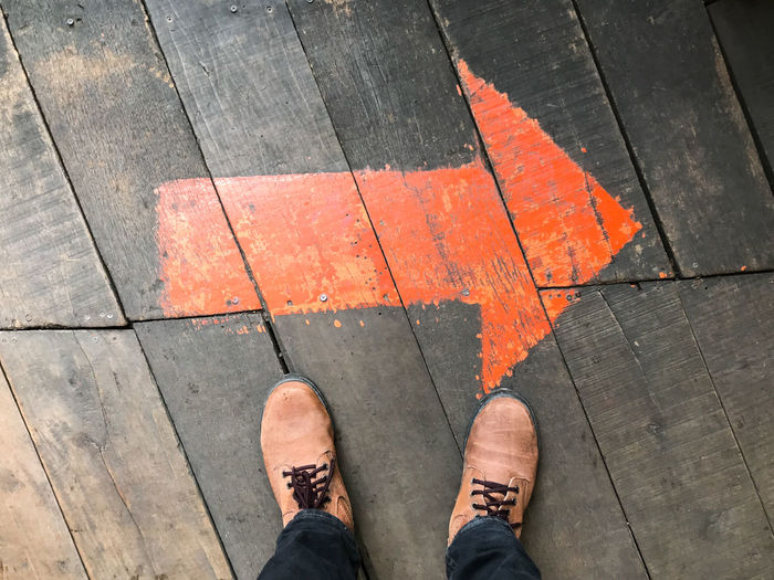 Low section of man standing on orange arrow sign on floorboard