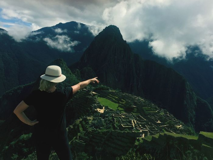 Woman pointing against mountain