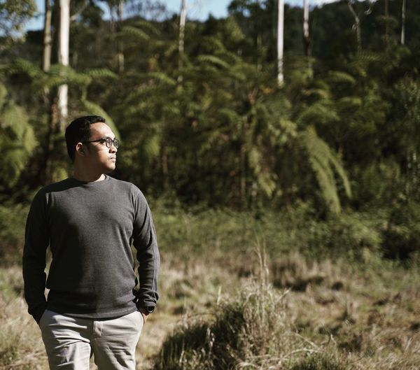 Man looking away while standing in forest