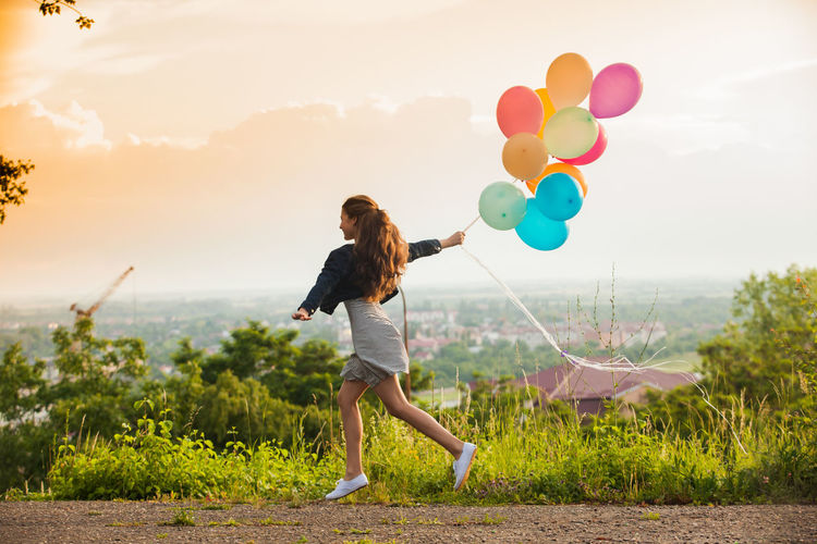 Rear view of woman holding balloons on field against sky