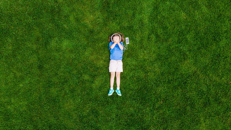 High angle view of girl listening to headphones while lying on grassy field