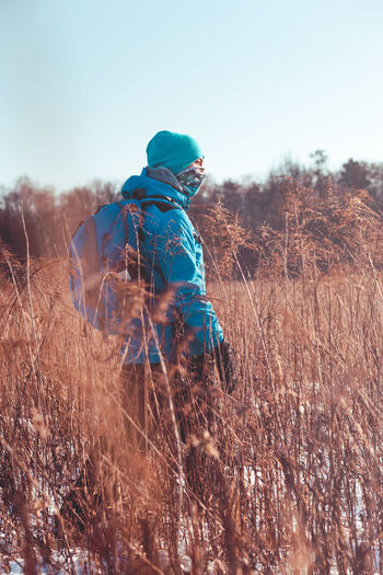 Woman With Backpack Standing Amidst Dried Plants On Field During Winter