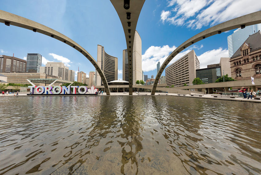 TORONTO, CANADA - JUNE 09, 2018: Beautiful wide view of the Nathan Phillips Square in the city Toronto Canada Architecture Bridge Bridge - Man Made Structure Building Building Exterior Built Structure City Cityscape Cloud - Sky Communication Day Financial District  Nathan Phillips Square Nature No People Office Building Exterior Outdoors River Sky Skyscraper Text Transportation Water Waterfront