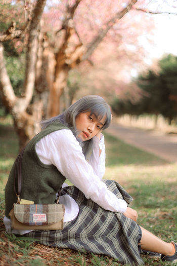 Full length of woman sitting against cherry tree