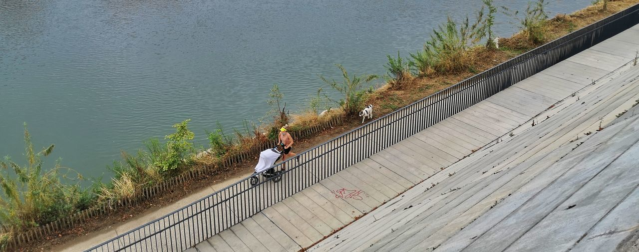 High angle view of people on footpath by lake