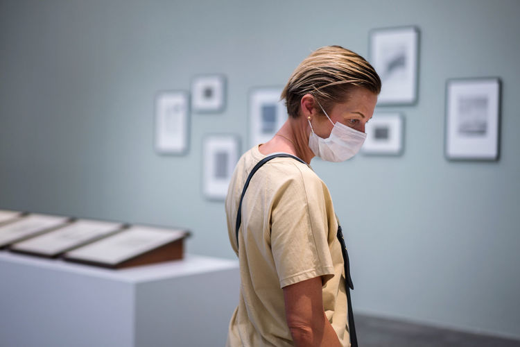Woman looking at the painting in the art gallery wearing face mask