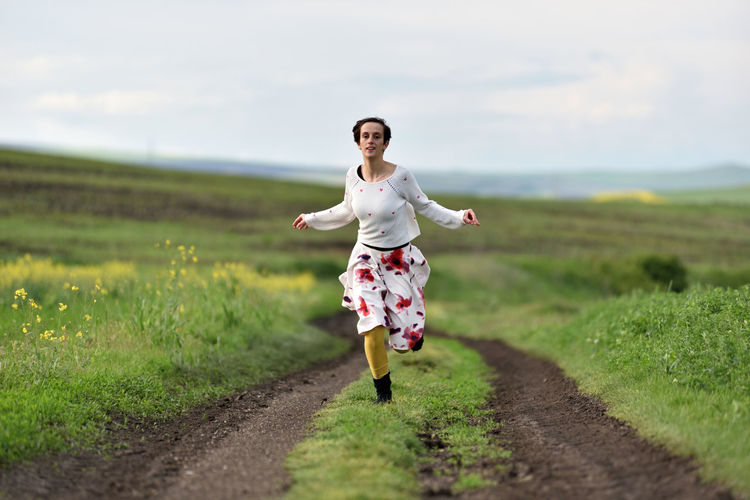 Full length of woman running on field