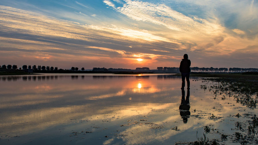 Silhouette person standing on sea shore against cloudy sky during sunset