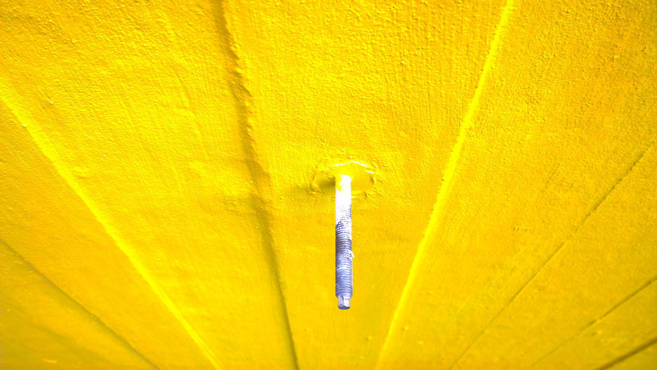 High Angle View Of Nail On Yellow Wall