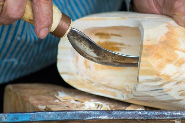 Close-up of man carving wood