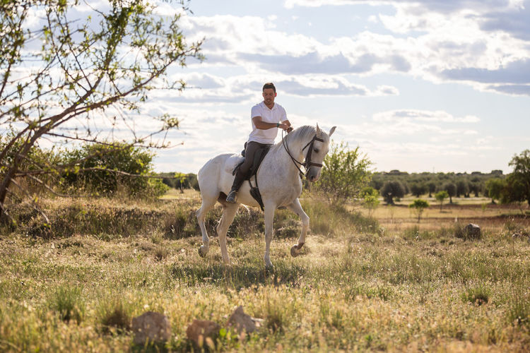 Full length of man riding horse on field