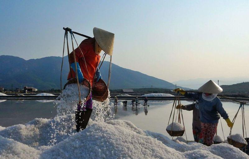 Woman working in salt flat against sky