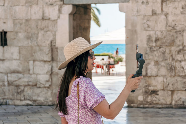 Woman photographing umbrella on wall