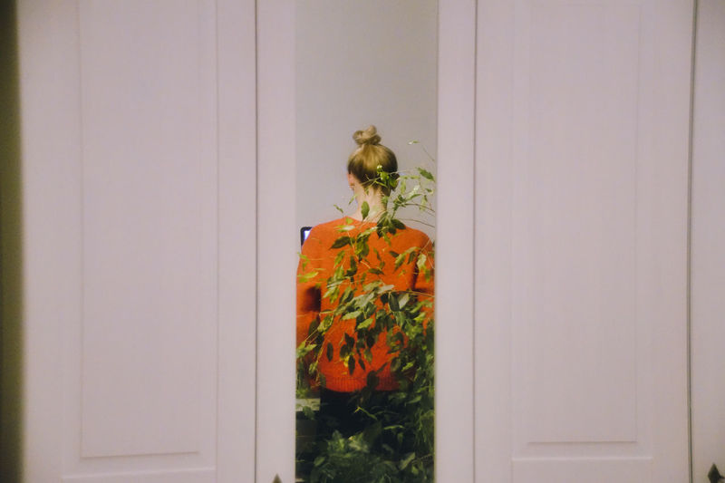 Rear view of woman reflecting on mirror