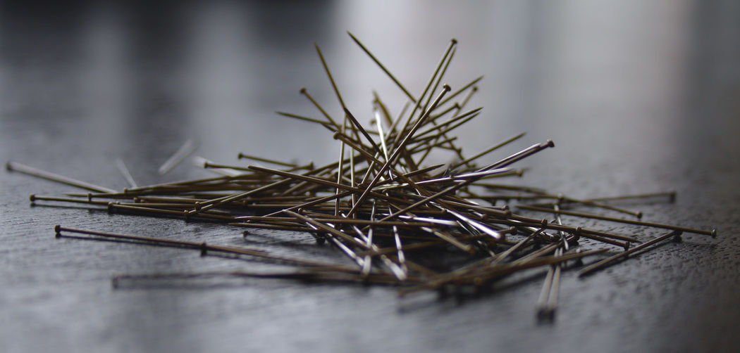 Close-up of straight pins on table