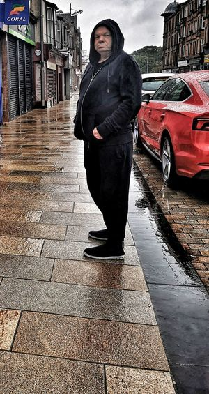 Full length of man standing on footpath in city