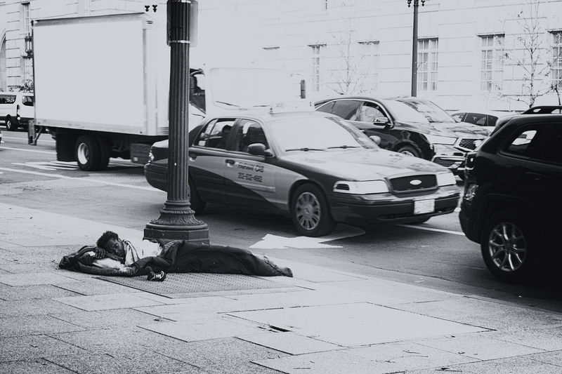View of man lying on car parked on road