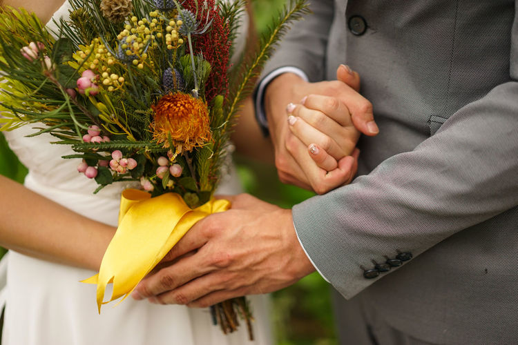 Midsection of bridal couple holding flower bouquet