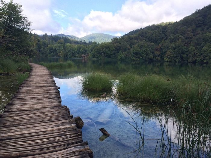 Wooden pathway at lake against sky at plitvice lakes national park
