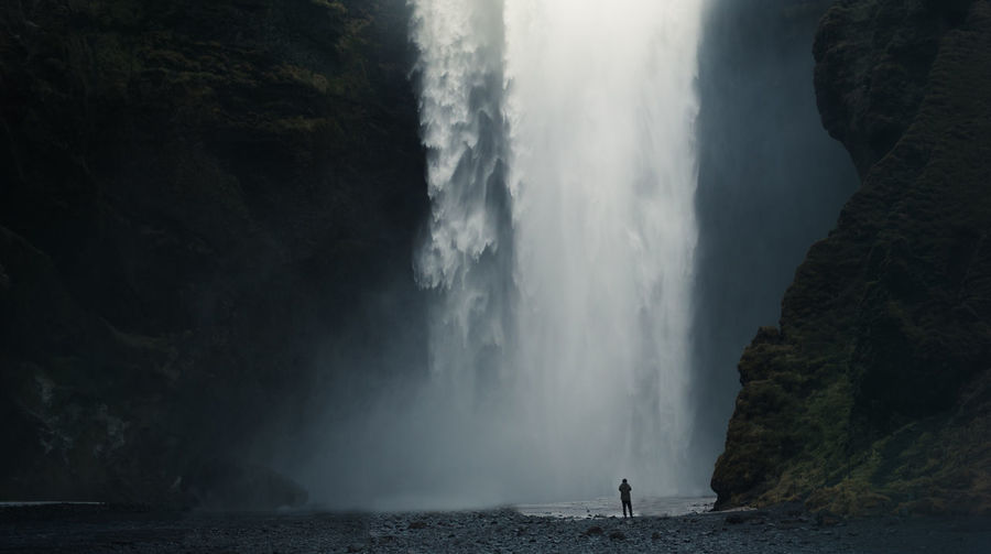 Mid distance view of person standing against waterfall