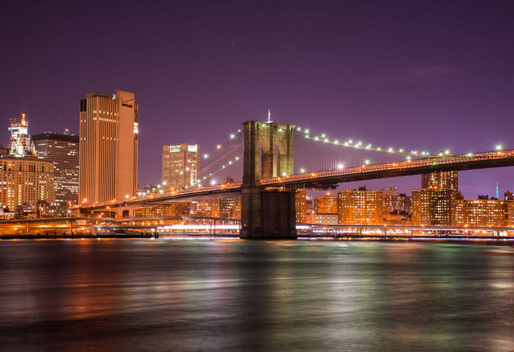 Brooklyn bridge over river by cityscape against sky at night
