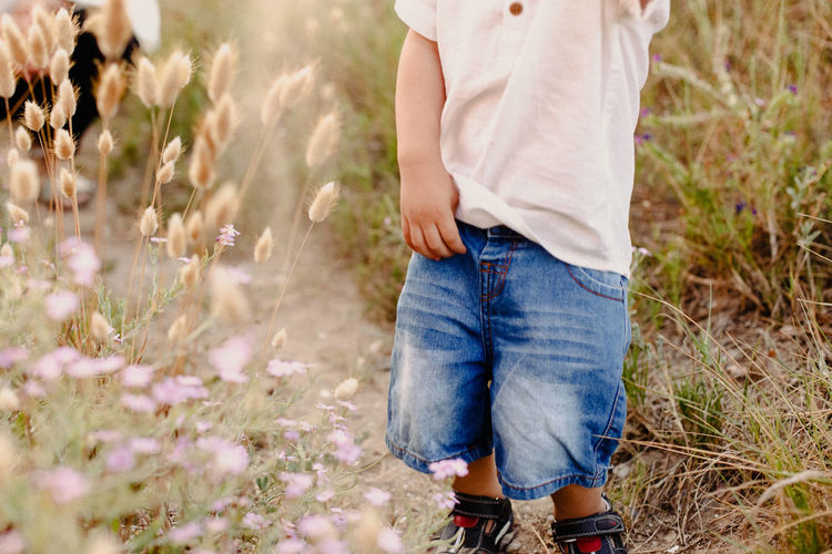Midsection of boy standing against grassy land