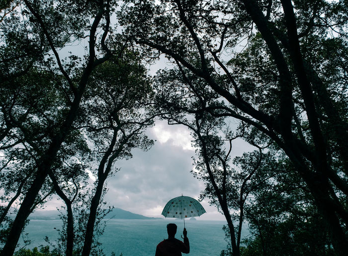 Woman standing by tree against sky