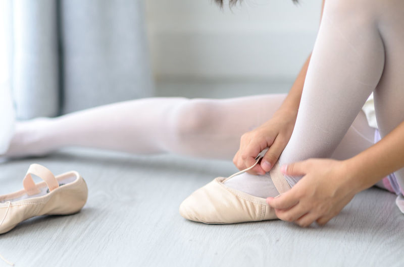 Low section of woman wearing ballet shoe