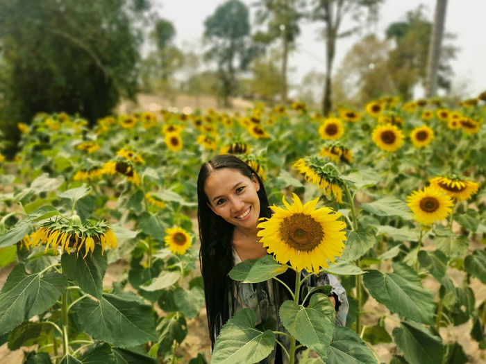 Portrait of young woman in sunflower field