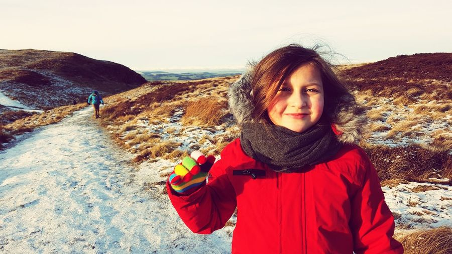 Portrait of smiling girl standing on snow covered landscape