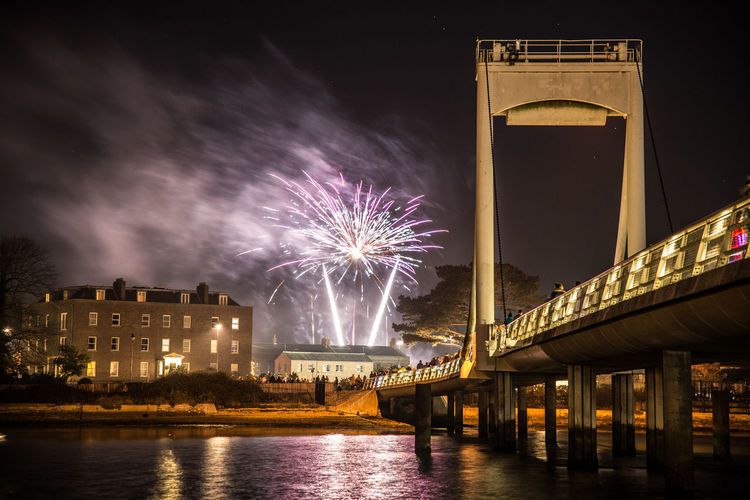 Firework Display Over River And Bridge Against Sky At Night