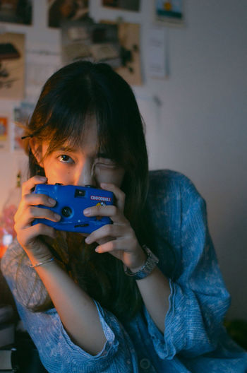 Portrait of girl holding camera at home
