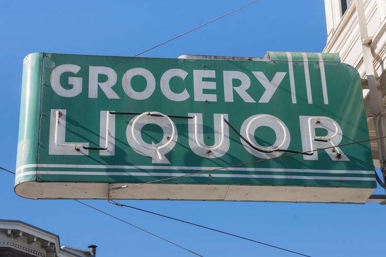 Low Angle View Of Grocery And Liquor Signboard