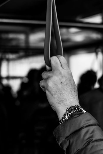 Close-up of man holding handle in train