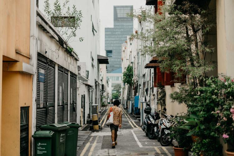 Rear view of man walking on alley in city