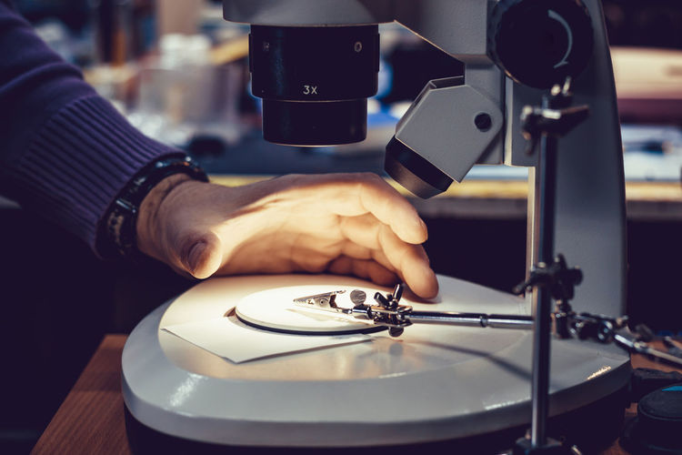 Cropped image of technician adjusting microscope slide indoors