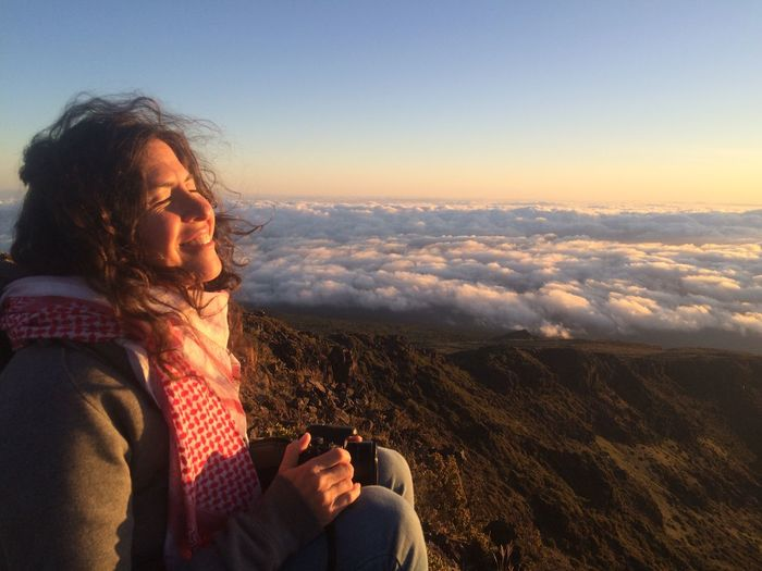 Sight of morning Bright Clear Sky Morning Morning Sky Above The Clouds Adult Angel Beautiful Woman Beauty In Nature Curly Hair Joy Mountain Mountaintop View Nature One Person Outdoors Red And White Scarf Sky Sunrise Warm Clothing White Smile Windy Woman Holding Camera Woman In Sunlight