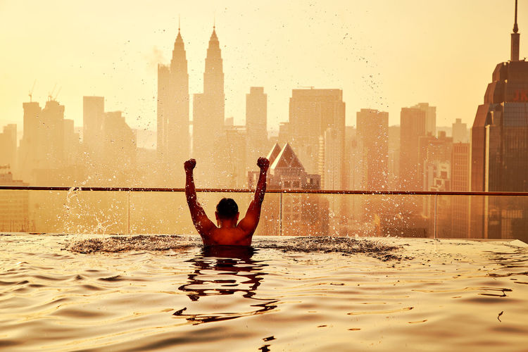 Rear view of man with arms raised in infinity pool during sunset