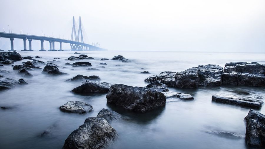 The view of Bandra worli sea link from Bandstand , Mumbai , India . Long Exposure Landscape City Getty Images City Cityscape Water Urban Skyline Sea Skyscraper Sunset Fog Bridge - Man Made Structure Horizon Suspension Bridge Steel Cable Overhead Cable Car Bay Of Water Seascape Tide