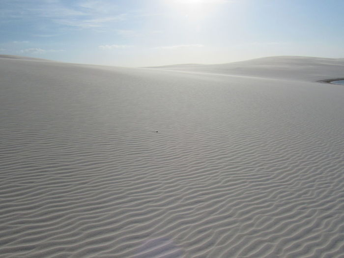Scenic view of sand dunes against sky