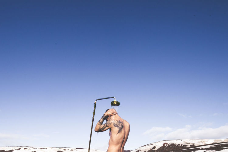 Rear View Of Man Bathing Against Blue Sky