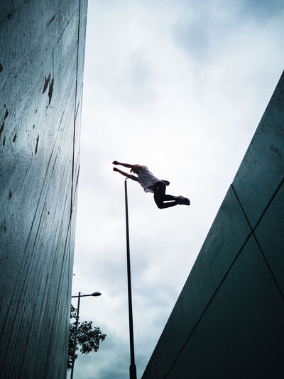 Low angle view of man flying over buildings against cloudy sky
