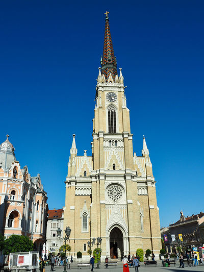 European Cities Novi Sad Serbia Eastern Europe Balkans Europe Outdoors Street Photography Travel Destinations Clear Blue Sky Architecture Public Places Facades Sunlight Built Structure Building Exterior Religion Belief Place Of Worship Spirituality Clock Tower Spire  Tourism Blue Historical Building