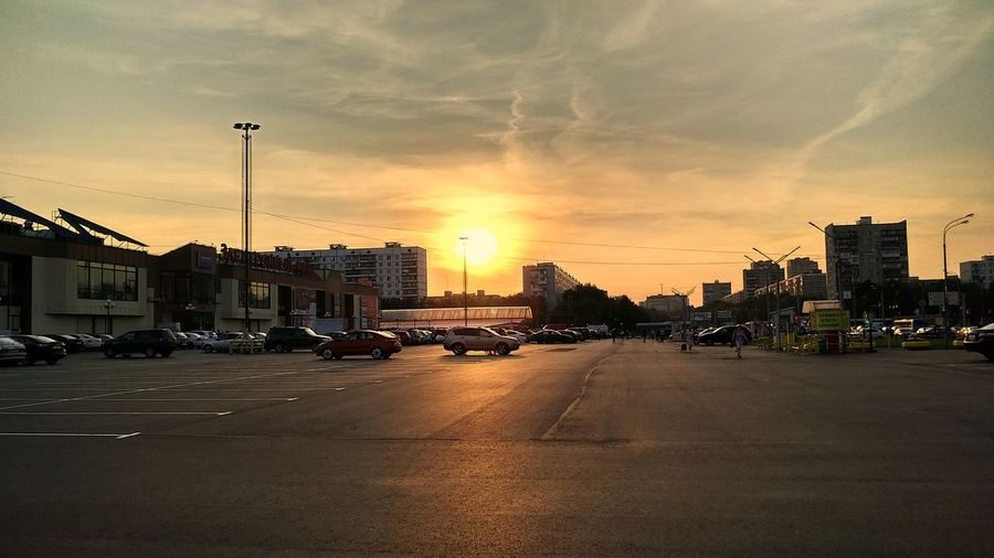 Cars on road by buildings against sky during sunset