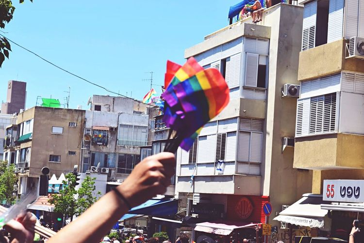 Cropped Hand Holding Rainbow Flags By Buildings Against Sky On Sunny Day