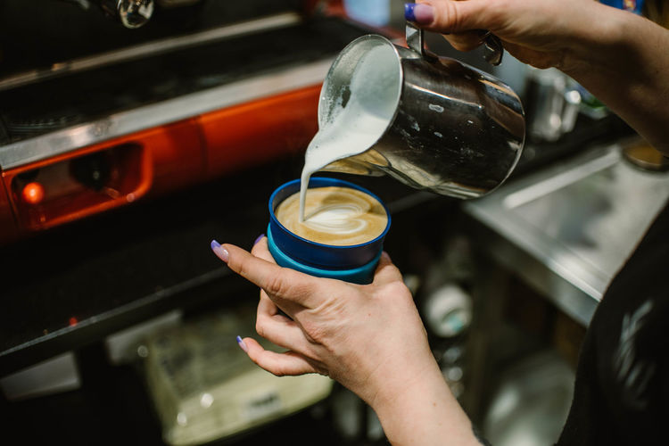 Cropped image of hand pouring coffee cup