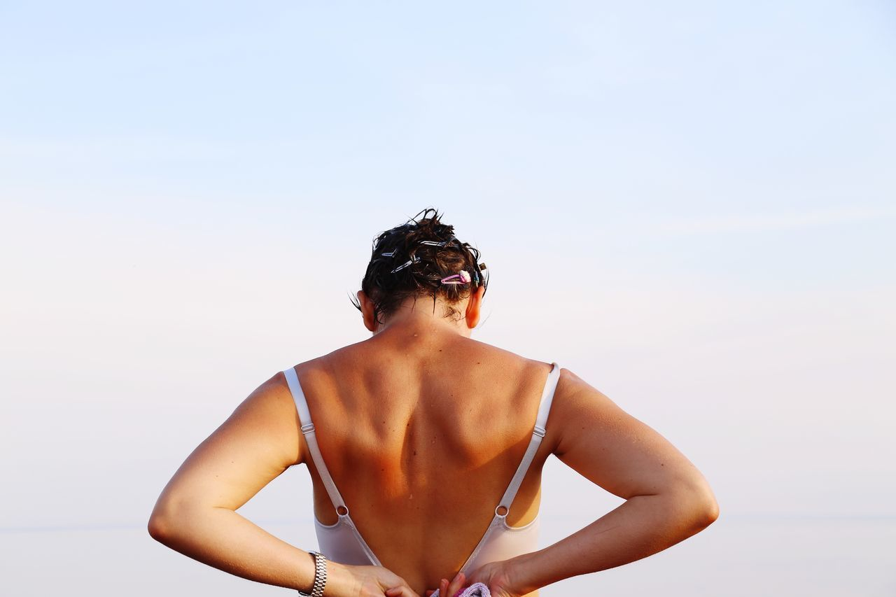Rear view of woman standing against sky