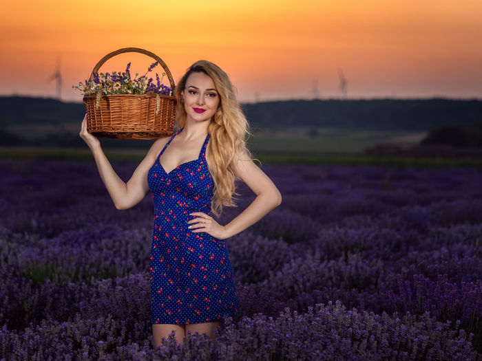 Beautiful young woman with yellow flowers on field against sky during sunset
